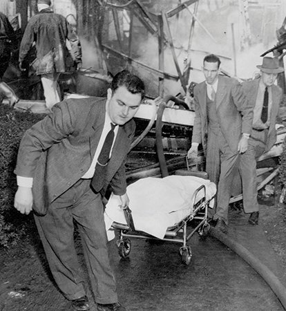 A black and white photo of two men in suits moving a dead person on a gurney away from a destroyed building | Blue Ridge Country