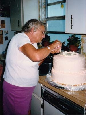 Janann Giles' mother decorates a wedding cake.